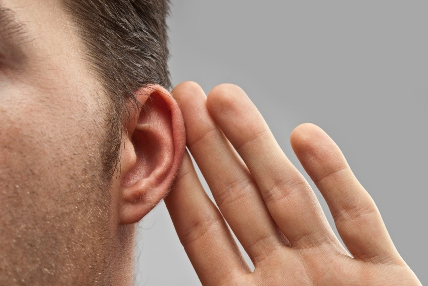Man with hearing loss holding a hand to his ear